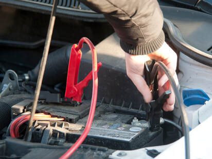 A man in brown jacket jumpstarting his car battery.