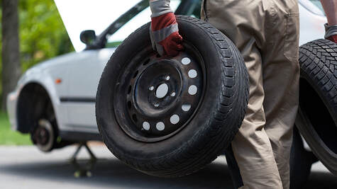A driver performing tire replacement on the roadside. white car change tire